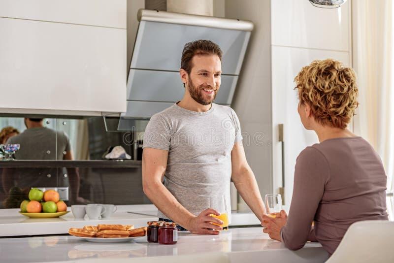 Счастливые пожененные пары имея завтрак дома стоковая фотография rf