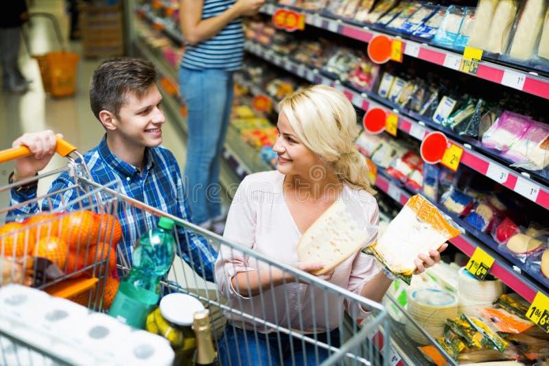 Счастливые положительные супруги покупая чеддер в разделе сыра стоковая фотография rf