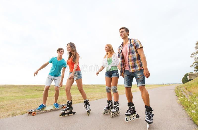 Счастливые подростки с rollerblades и longboards стоковая фотография rf
