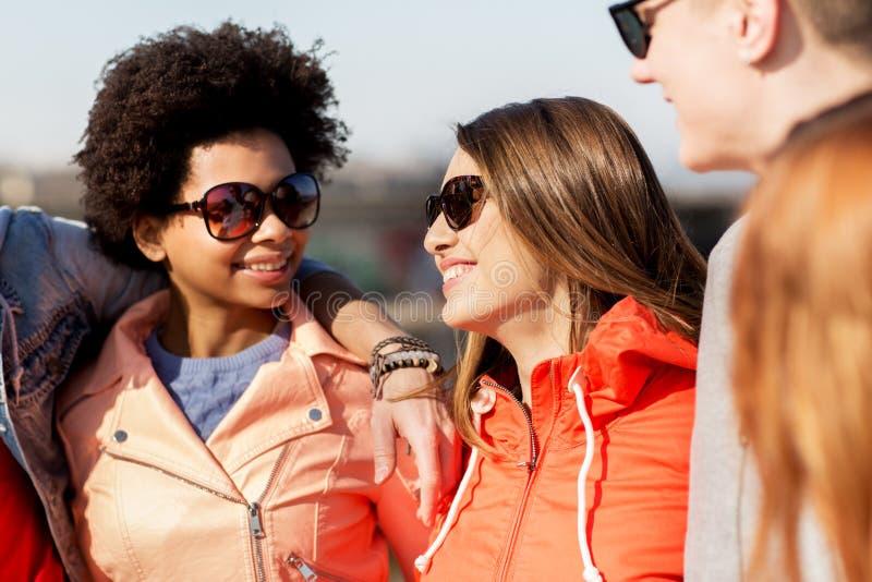 Счастливые подростковые друзья в тенях говоря на улице стоковая фотография rf