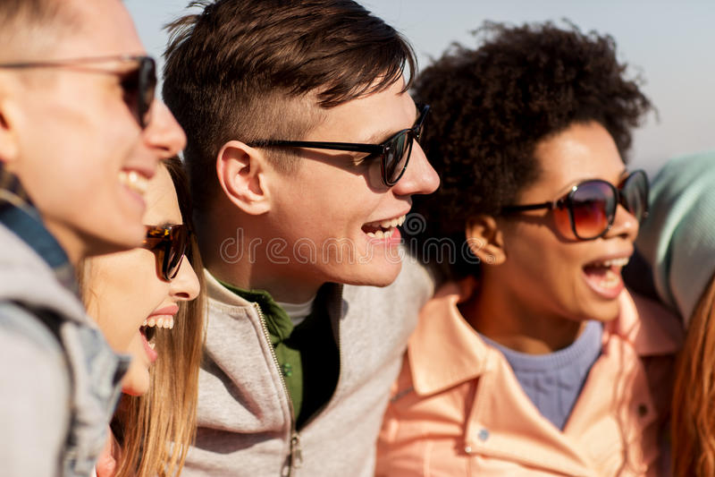 Счастливые подростковые друзья в тенях смеясь над outdoors стоковое изображение