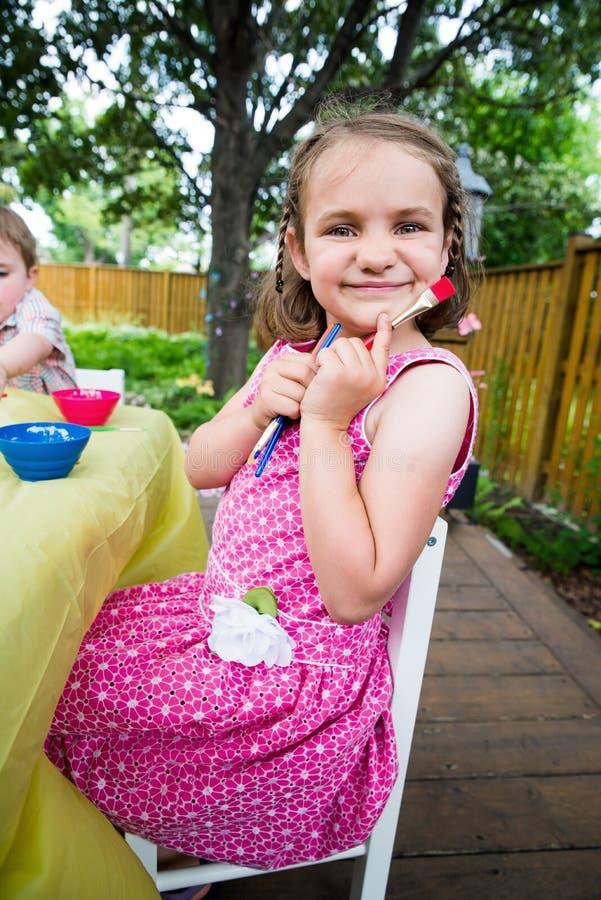 Счастливые представления маленькой девочки с кистями стоковое изображение