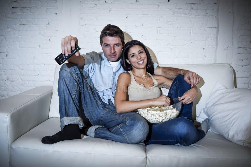 Счастливые привлекательные пары имея потеху дома наслаждаясь смотрящ телевидение ослабили стоковая фотография