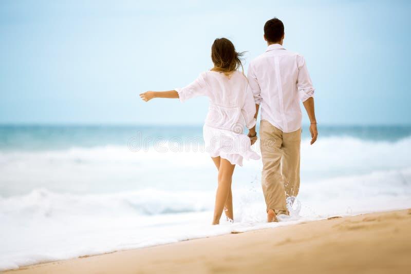Счастливые романтичные молодые пары идя на пляж стоковое изображение rf