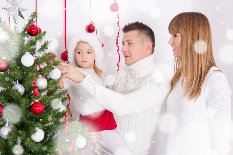 Счастливые родители и дочь украшая рождественскую елку стоковое фото