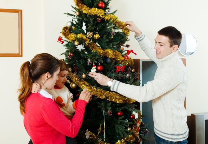 Счастливые родители и ребенок украшая рождественскую елку стоковое изображение