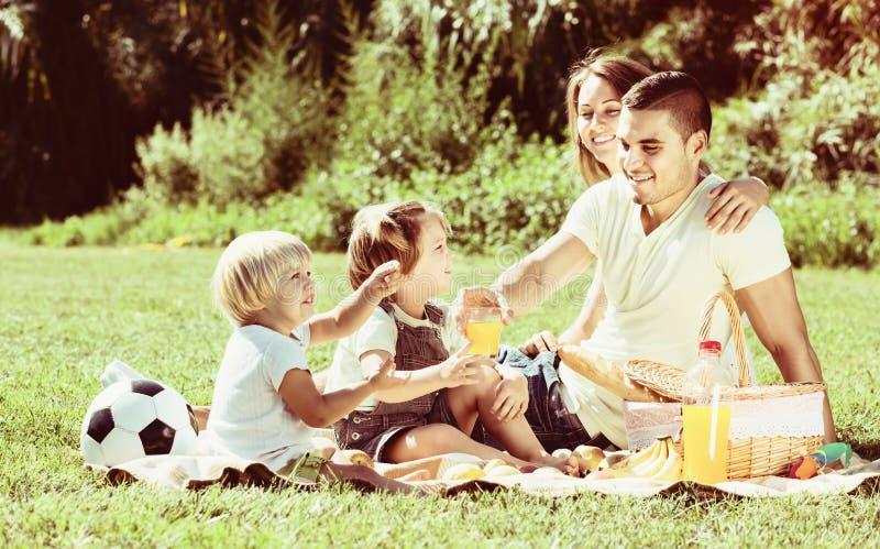 Счастливые родители при маленькие девочки имея пикник стоковые изображения rf