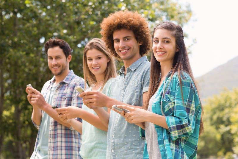Счастливые друзья в парке используя их телефоны стоковые фотографии rf