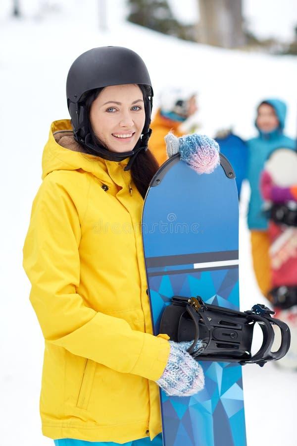 Счастливые друзья в шлемах с сноубордами стоковые изображения rf