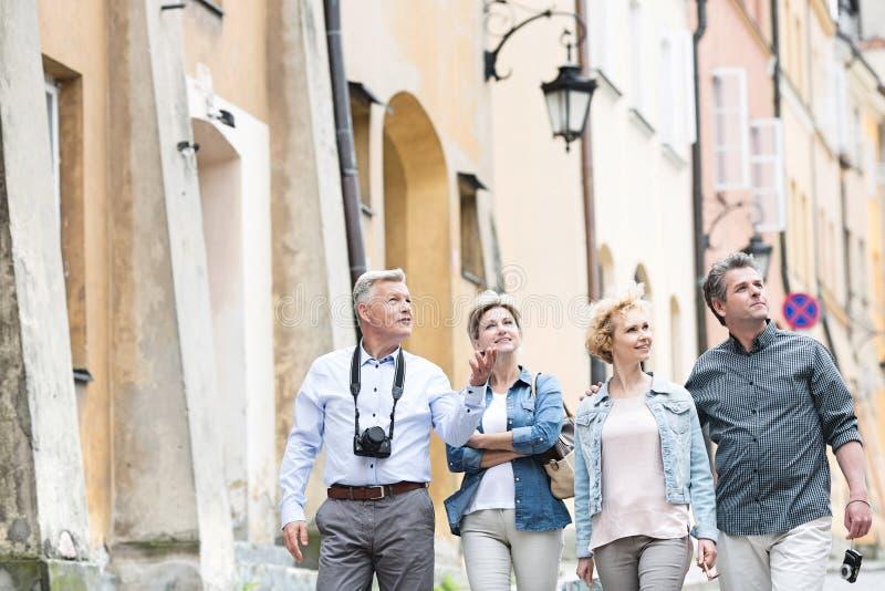 Счастливые друзья говоря пока идущ в город стоковое изображение rf