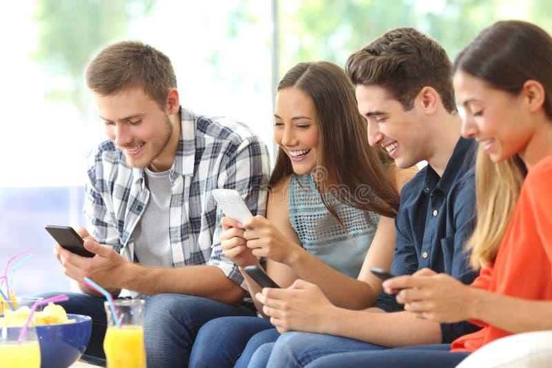 Счастливые друзья используя их мобильные телефоны