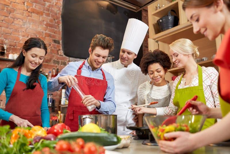 Счастливые друзья и шеф-повар варят варить в кухне стоковые фото