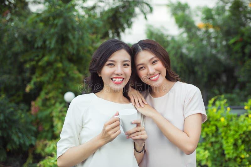 Счастливые друзья молодых женщин хорошо одели усмехаться пока стоящ к стоковое изображение rf