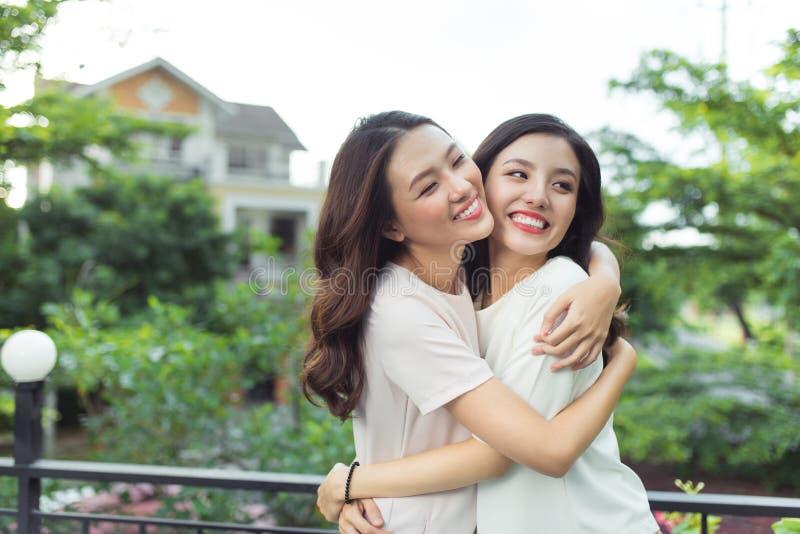 Счастливые друзья молодых женщин хорошо одели усмехаться пока стоящ к стоковая фотография rf