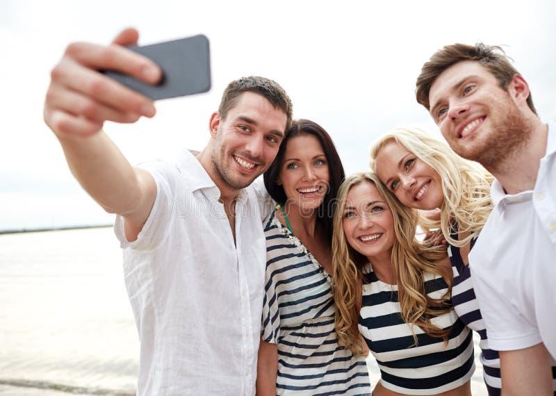 Счастливые друзья на пляже и selfie принимать стоковая фотография