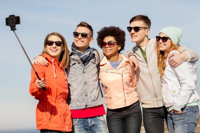 Счастливые друзья принимая selfie smartphone outdoors стоковая фотография rf