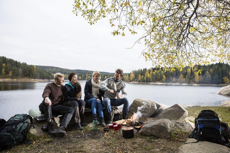 Счастливые друзья располагаясь лагерем дальше Lakeshore стоковая фотография rf