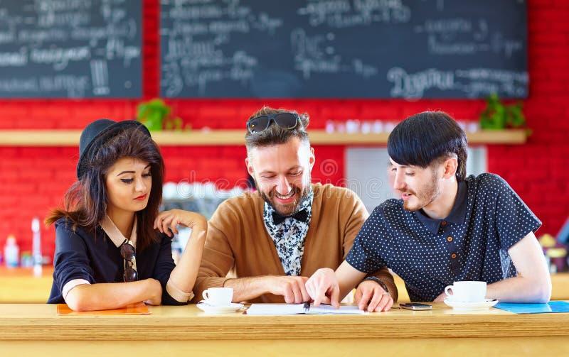 Счастливые друзья сидя в кафе, изучая стоковое фото rf
