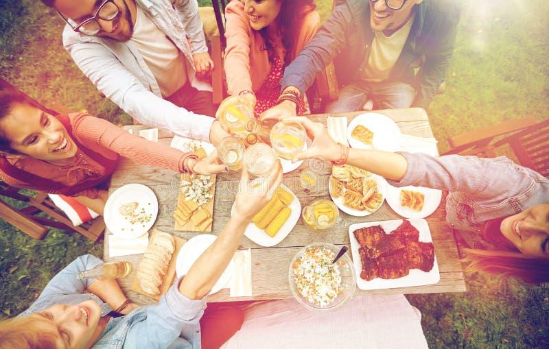 Счастливые друзья с пить на приём гостей в саду лета стоковое изображение rf