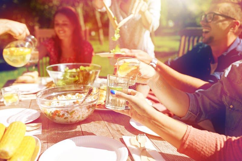 Счастливые друзья с пить на приём гостей в саду лета стоковые изображения