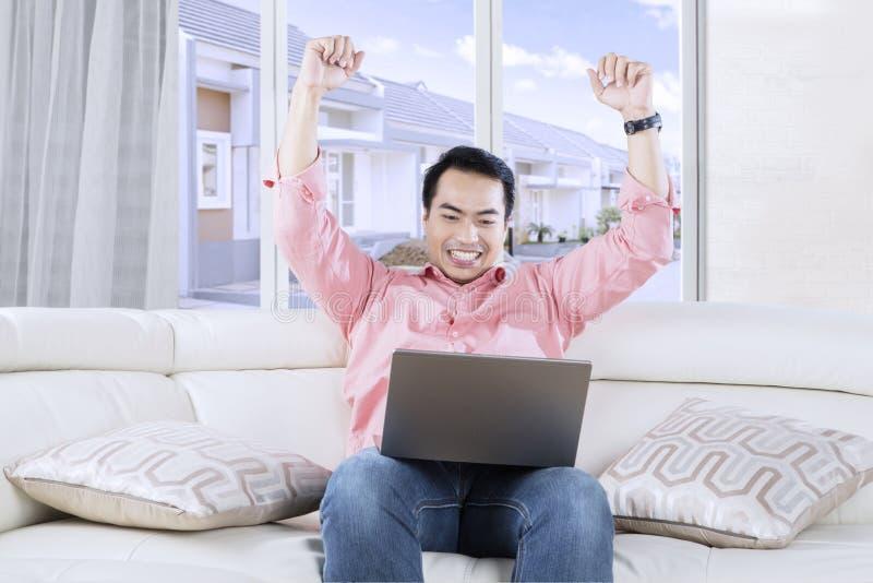 Счастливые руки повышения человека с компьтер-книжкой стоковое изображение