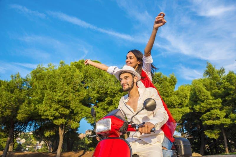Счастливые свободные пары свободы управляя самокатом возбужденным на летних отпусках отдыхают стоковое изображение