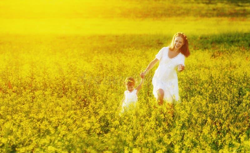 Счастливые семья, мать и ребенок l маленькая дочь бежать на mea стоковая фотография rf