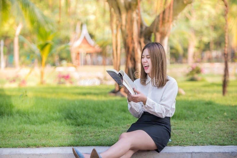 Счастливые смеяться над и улыбка бизнес-леди читая книгу стоковые фото