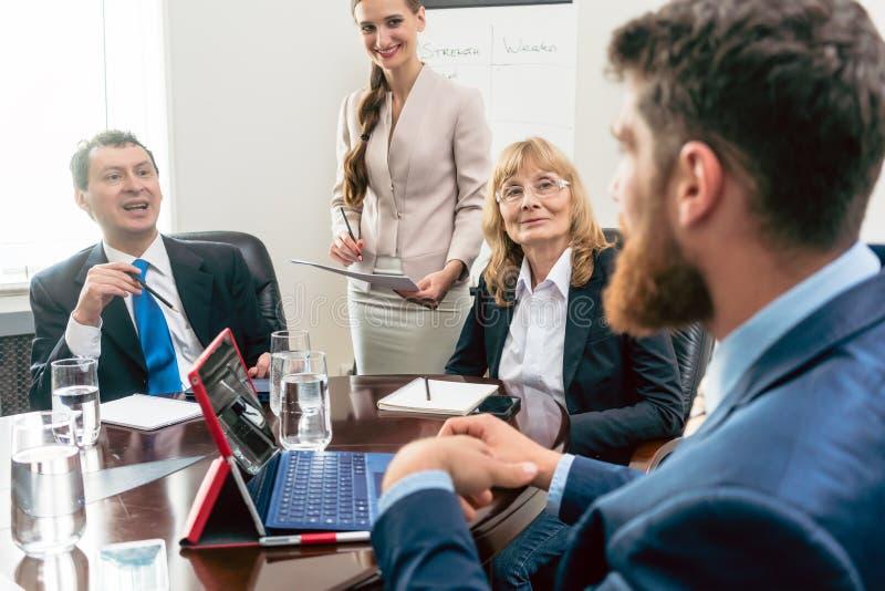 Счастливые средн-постаретые менеджеры слушая к их более молодому коллеге стоковые изображения