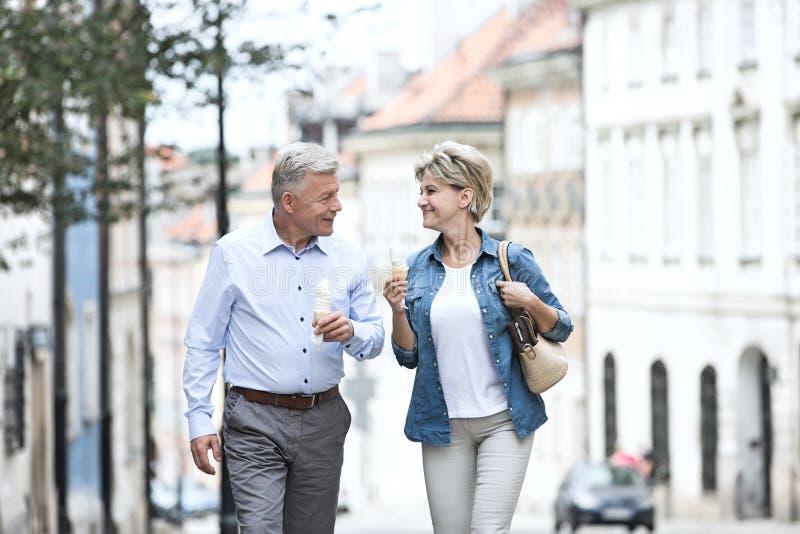 Счастливые средн-постаретые пары смотря один другого пока держащ конусы мороженого в городе стоковое изображение rf