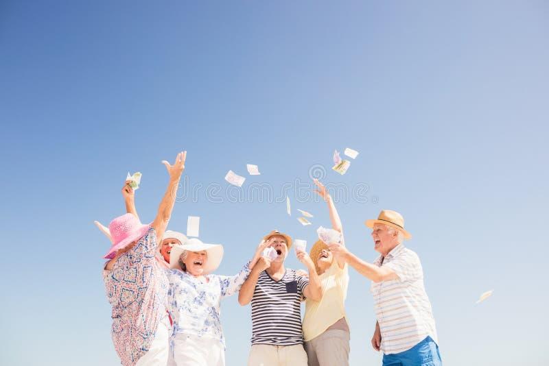 Счастливые старшие бросая деньги стоковая фотография