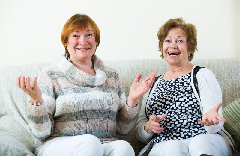 Download Счастливые старшие женщины представляя внутри помещения и смеясь над Стоковое Фото - изображение насчитывающей обсуждение, женщина: 81800296