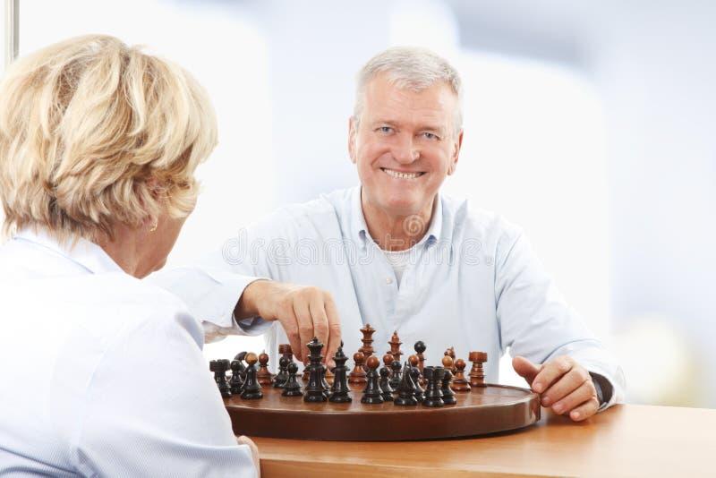 Счастливые старшие пары играя шахмат стоковые изображения