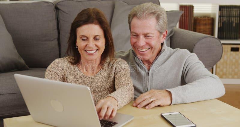 Счастливые старшие пары используя компьтер-книжку на журнальном столе стоковая фотография