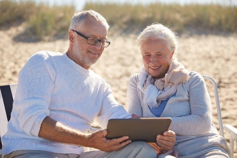 Счастливые старшие пары с ПК таблетки на лете приставают к берегу стоковое изображение