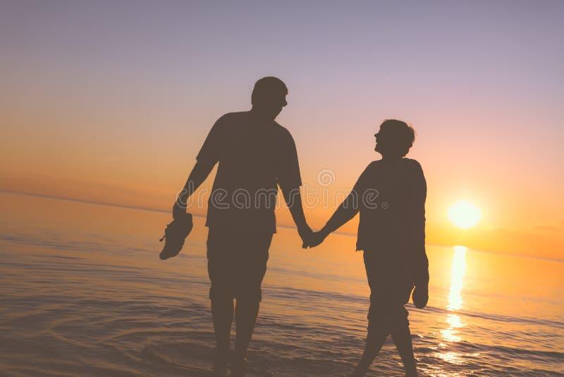 Счастливые старшие силуэты пар на пляже стоковое фото rf