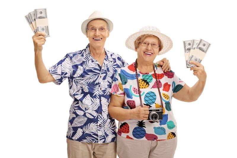 Счастливые старшие туристы представляя с пачками денег стоковые изображения