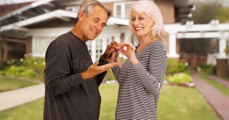 Счастливые старшии возбужденные для их нового купленного дома стоковая фотография