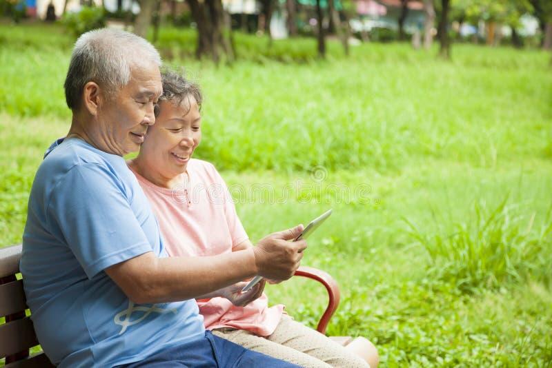 Счастливые старшии с ПК таблетки стоковое фото