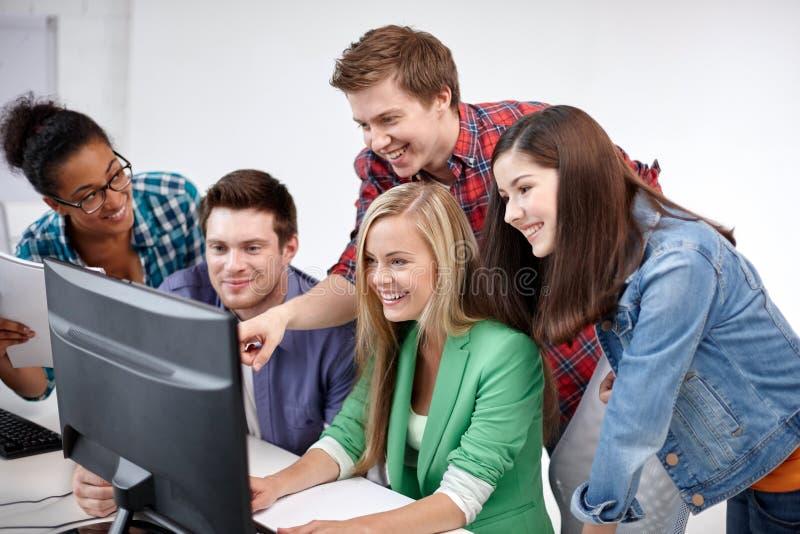 Счастливые студенты средней школы в классе компьютера стоковые фото
