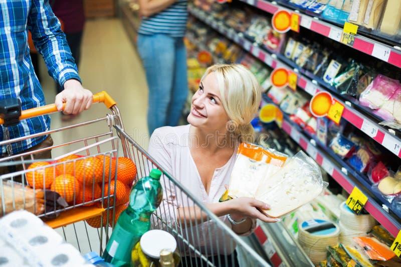 Счастливые супруги покупая чеддер в разделе сыра стоковая фотография