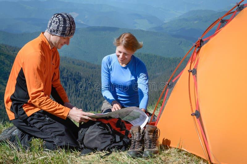 Счастливые туристы с картой в горах Взгляд сверху стоковое фото