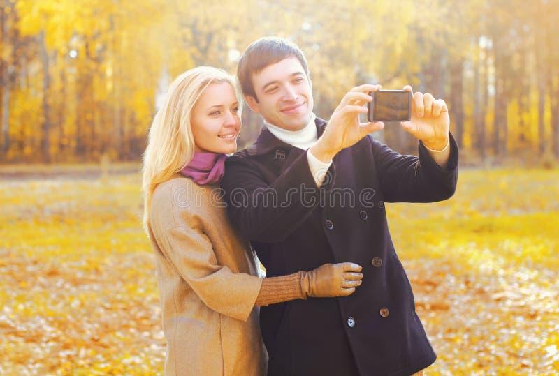 Счастливые усмехаясь молодые пары совместно принимая автопортрет изображения на smarphone в солнечной осени стоковое фото rf