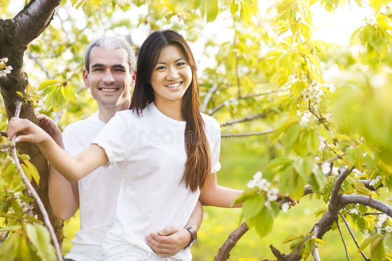 Счастливые усмехаясь пары в саде влюбленности весной стоковые изображения rf