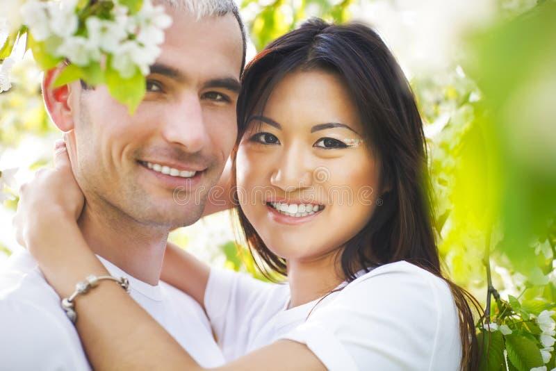 Счастливые усмехаясь пары в саде влюбленности весной стоковое изображение rf
