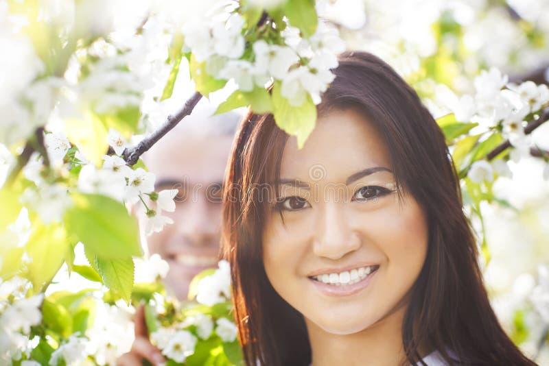 Счастливые усмехаясь пары в саде влюбленности весной стоковые фото