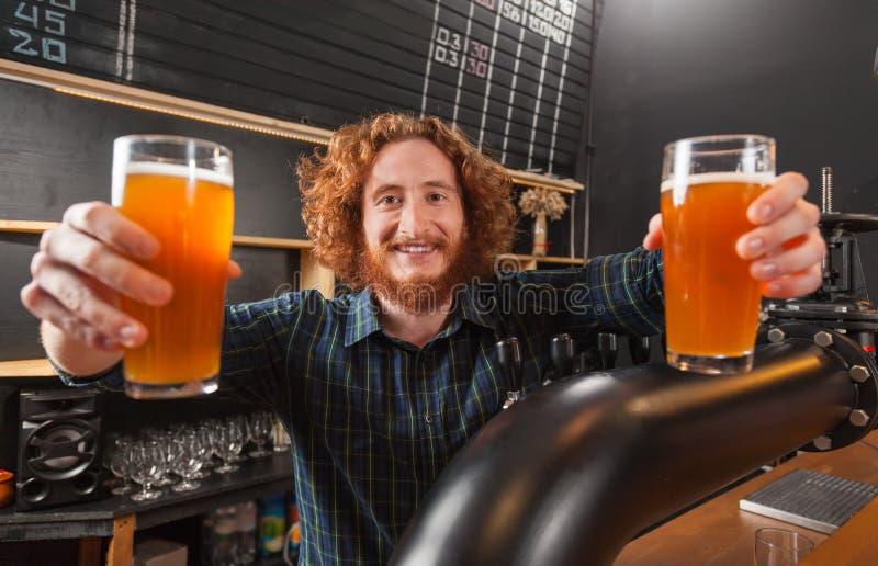 Счастливые усмехаясь стекла пива владением 2 бармена, стойка на счетчике, заказе сервировки бармена стоковые изображения rf