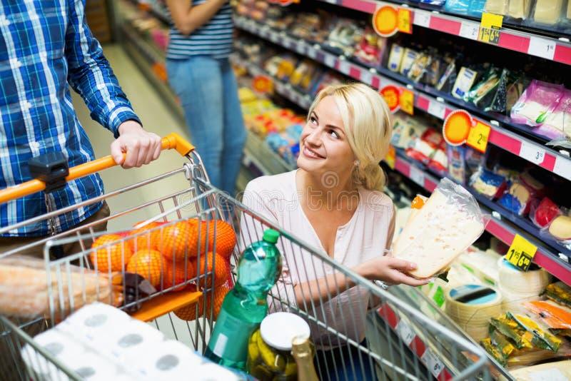 Счастливые усмехаясь супруги покупая чеддер в разделе сыра стоковая фотография rf