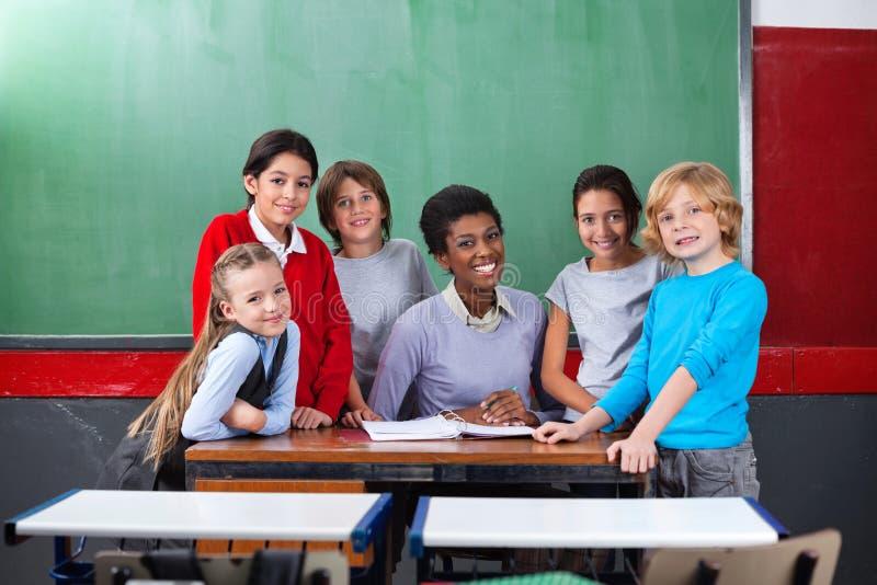 Счастливые учитель и школьники стоковое изображение rf