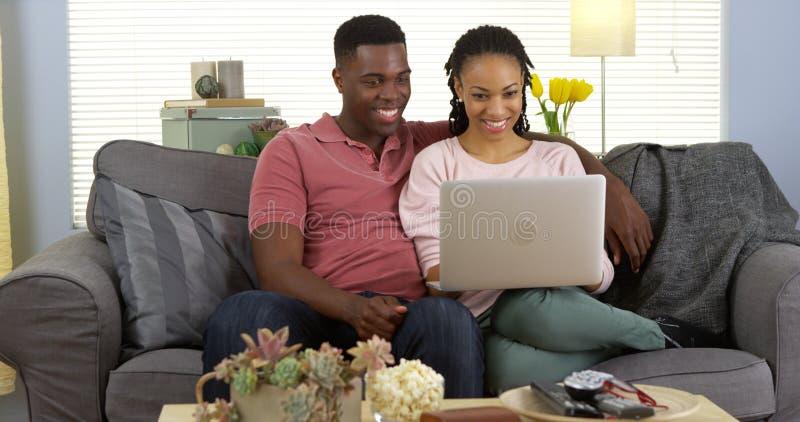 Счастливые черные пары на интернете просматривать кресла с компьтер-книжкой стоковое изображение